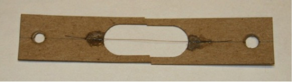 Fig. 4.  Test grip used to hold the hair. The hair is glued to rigid fiberboard to prevent stress concentrations from forming from mechanical clamping on the hair itself.